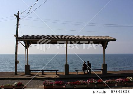 下灘駅で海を見ながら電車を待つ夫婦 67345338