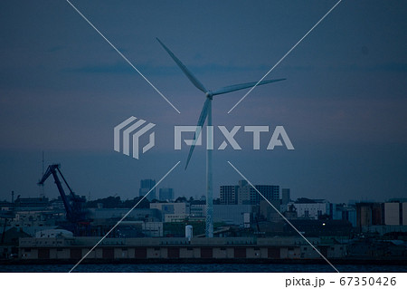 港町にそびえ立つ風力発電用のタービン 67350426