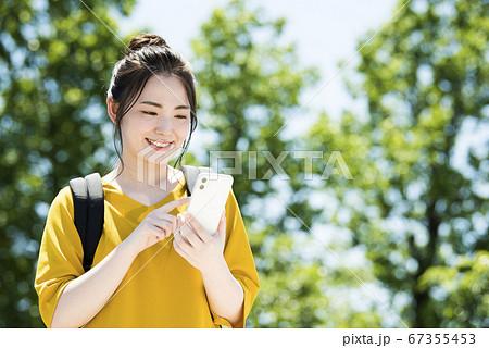 スマホを操作する若い女性 67355453