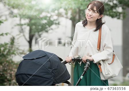 住宅街をベビーカーを押して歩く母親   67363556