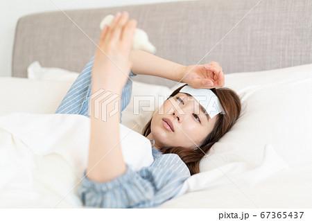 発熱してベッドの中で体温を測る若い女性 67365437