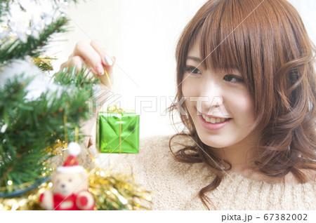クリスマスツリーを飾る女性 67382002