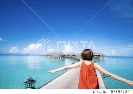 モルジブの水上コテージへ向かう赤いドレスの女性(ピント女性) 67397184