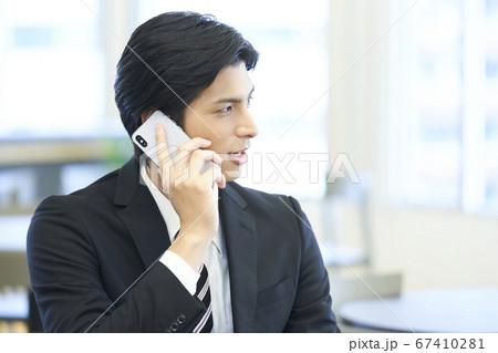電話をかける若いビジネスマン スーツ 67410281