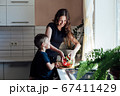 Little son helps mom cook vegetable salad in the kitchen 67411429