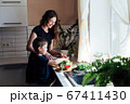 Little son helps mom cook vegetable salad in the kitchen 67411430