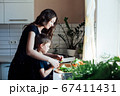 Little son helps mom cook vegetable salad in the kitchen 67411431