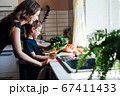 Little son helps mom cook vegetable salad in the kitchen 67411433