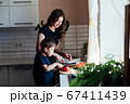 Little son helps mom cook vegetable salad cuts vegetables in kitchen 67411439