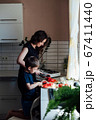 Little son helps mom cook vegetable salad cuts vegetables in kitchen 67411440