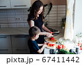 Little son helps mom cook vegetable salad cuts vegetables in kitchen 67411442