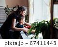 Little son helps mom wash vegetables in the kitchen 67411443