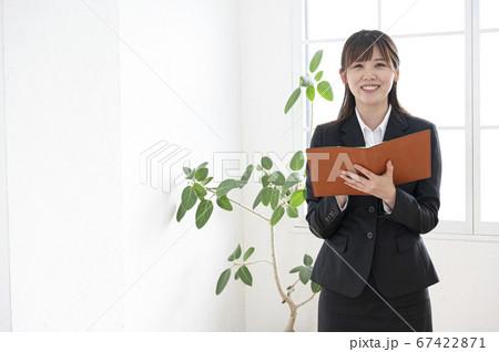 スーツ姿で立って手帳を見る若い女性 67422871