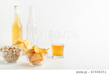 Snack and beer. Chips, pistachios and nachos in plates, half a glass of beer, full bottle and empty bottle 67440251