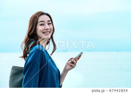スマホを操作する海に居る若い女性 67442834