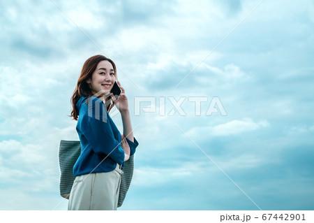空を背景にスマホで電話するカジュアル姿のビジネスウーマン  67442901