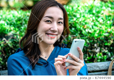 公園でスマートフォンを操作する若い女性 67444590