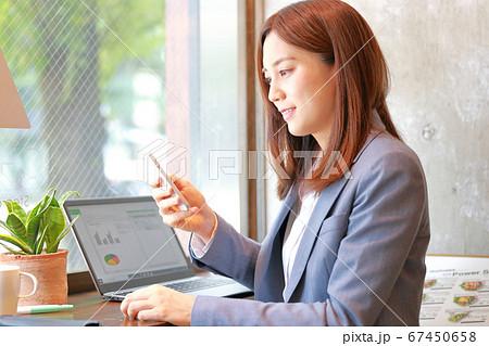 スマホを見て笑顔のビジネスウーマン 67450658