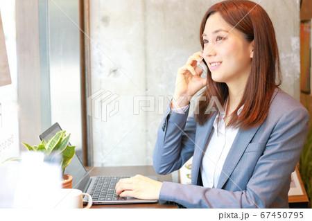 スマホで相手が話すのを聞くビジネスウーマン 67450795
