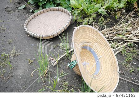 畑の土に置かれたカゴと麦わら帽子 67451165