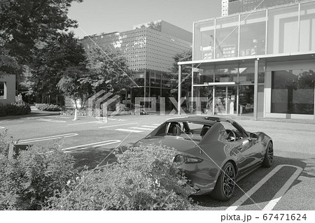 広い駐車場に停められたオープンカー 67471624