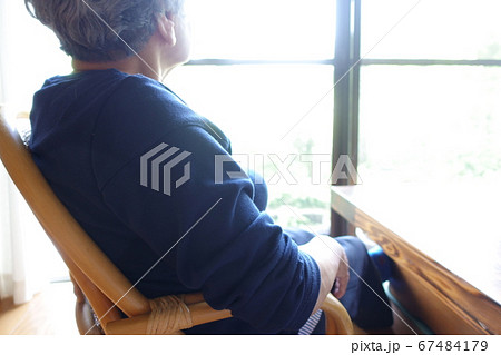 窓辺に座り外を見るおばあちゃん シニア女性 67484179