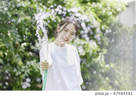 若い女性 水まき 夏のイメージ 67484392