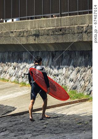 湘南鎌倉海岸(稲村ケ崎)でサーフィンを楽しみ浜辺を後にするサーファー 67487014