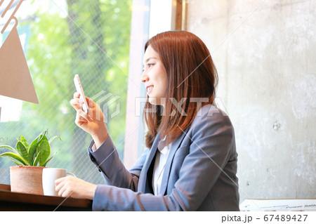 カフェのカウンター席でスマホを持つ女性 67489427