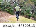 キャンプ道具を自転車に積んで進む男性 67509313