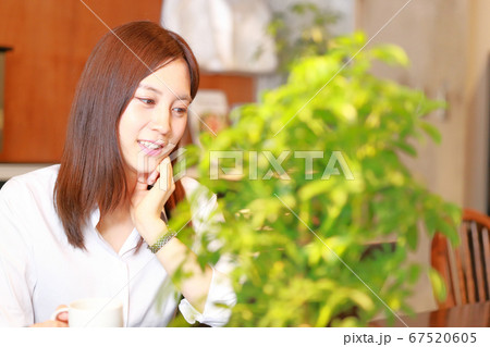 カフェで笑顔でコーヒーカップを持つ女性 67520605