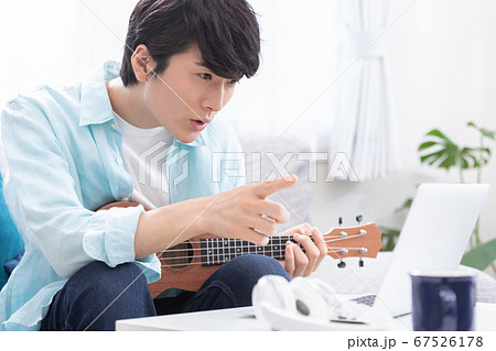 オンラインで楽器(ウクレレ)のレッスンを受ける若い男性 67526178