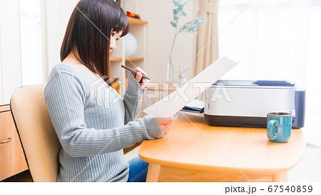 書類を確認する女性 様々な書類 テレワーク 申請 証明 申込 請求 願書 履歴書など 16:9 67540859