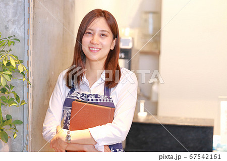 メニュー表を持って微笑むカフェのスタッフ 67542161