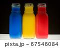 ガラス瓶に入れた三原色の色水 67546084