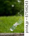 夏の公園に水を入れたガラス瓶が落ちる瞬間の様子 67546243