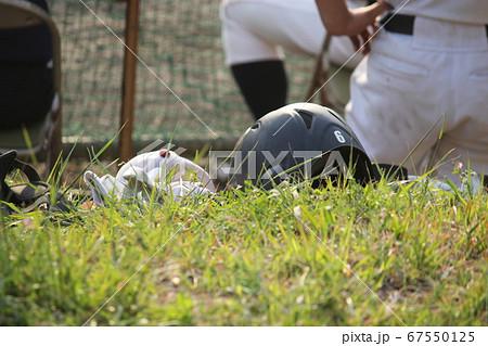 高校野球・試合の中で次の打者を待つヘルメットとバッティング手袋 67550125