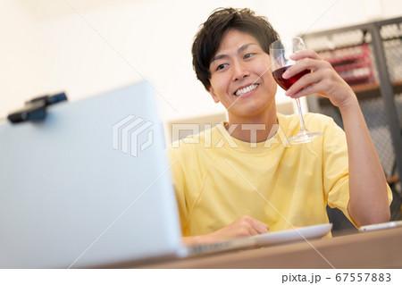 オンライン飲み会 赤ワインを飲む若い男性 67557883