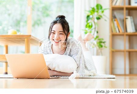 リビングでパソコンを使う若い女性 67574039