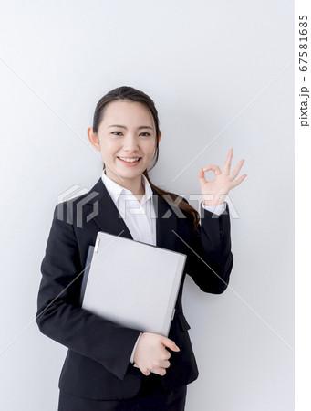 ノートパソコンを抱えてOKサインをする笑顔のビジネスウーマン 67581685