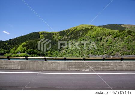 新緑の奥多摩湖 提頂の道路と背景の山々 67585145