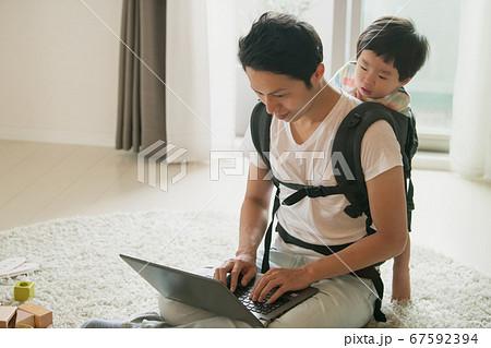 子供の世話をしながら在宅勤務をする父親イメージ 67592394