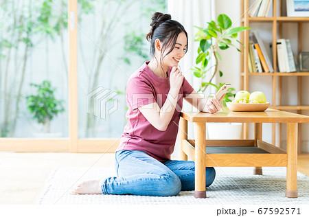 リビングでスマホを操作する若い女性 67592571