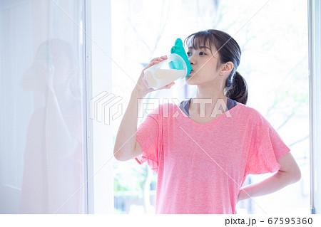 プロテインを飲むトレーニング中の若い女性 67595360
