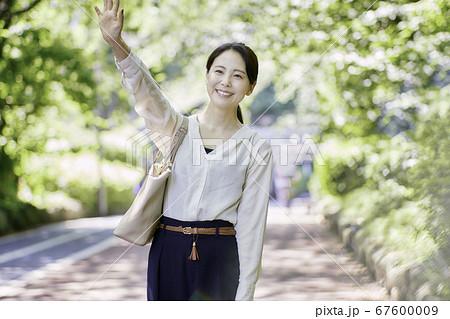 手を振る若い女性のポートレート (屋外) 67600009