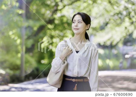 木々の中佇む若い女性のポートレート (屋外) 67600690
