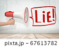Man's hand holding red and white megaphone against grungy white wall with big speech bubble that says 'Lie' 67613782