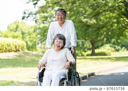 車椅子で公園を散歩するシニアのカップル 67615736
