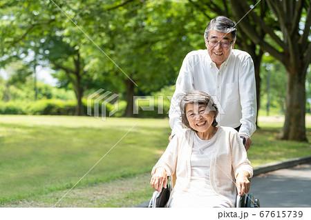 車椅子で公園を散歩するシニアのカップル 67615739