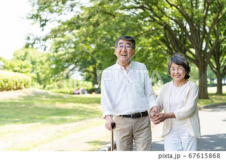 公園を散歩してリハビリをするシニアのカップル 67615868